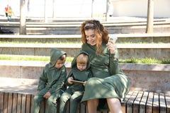 Szczęśliwa matka z dziećmi w modnych ubrań rodzinnym spojrzeniu w parku obrazy royalty free