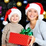 Szczęśliwa matka z dziecko chwyta pudełkiem z prezentem na bożych narodzeniach Obrazy Royalty Free