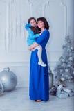Szczęśliwa matka z jej córką w długim błękit sukni stojaku blisko choinki Obraz Royalty Free