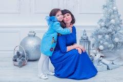 Szczęśliwa matka z jej córką w długim błękit sukni stojaku blisko choinki Fotografia Royalty Free