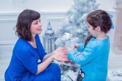 Szczęśliwa matka z jej córką w długim błękit sukni stojaku blisko choinki Obrazy Royalty Free