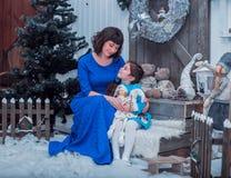 Szczęśliwa matka z jej córką w długim błękit sukni stojaku blisko choinki Zdjęcia Royalty Free