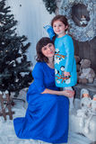 Szczęśliwa matka z jej córką w długim błękit sukni stojaku blisko choinki Fotografia Stock