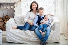 Szczęśliwa matka z jej dziećmi ma zabawę w żywym pokoju Obrazy Stock