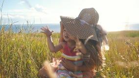 Szczęśliwa matka z małą córką siedzi w polu i błaź się wokoło zbiory