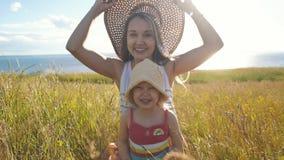 Szczęśliwa matka z małą córką siedzi w polu i błaź się wokoło zdjęcie wideo