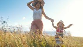 Szczęśliwa matka z małym córka bieg przez pole zbiory wideo