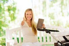 Szczęśliwa matka z pastylka komputerem osobistym i spacerowicz w parku Zdjęcia Stock