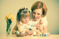Szczęśliwa matki i dziecka córka z szczotkarskimi barwi Easter jajkami obrazy royalty free
