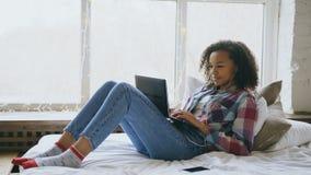 Szczęśliwa mieszana biegowa dziewczyna ma wideo gadkę z przyjaciółmi używa laptop kamerę podczas gdy kłamający na łóżku Zdjęcie Royalty Free