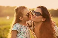 Szczęśliwa moda dzieciaka dziewczyna szepcze jej matki i patrzeje na natury tle sekret w modnych okularach przeciwsłonecznych w p obrazy royalty free