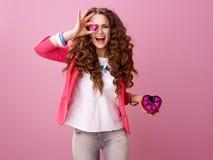 Szczęśliwa modna kobieta pokazuje serce kształtował czekoladowych cukierki Zdjęcia Stock