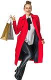 Szczęśliwa modna kobieta w czerwonym żakiecie na bielu z torba na zakupy Obrazy Stock