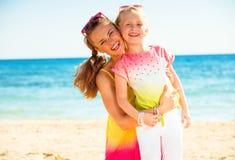 Szczęśliwa modna matka i dziecko w kolorowych ubraniach na seacoast zdjęcia stock