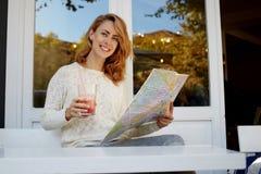 szczęśliwa modniś dziewczyna patrzeje w miasto przewdonika następnym miejscu odwiedzać podczas gdy śniadanie w wygodnej restaurac Fotografia Royalty Free