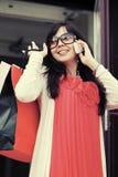 Szczęśliwa mody kobieta dzwoni na telefonie komórkowym z torba na zakupy Zdjęcie Royalty Free