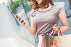 Szczęśliwa mody kobieta z torbą używać telefon komórkowego, centrum handlowe Fotografia Stock