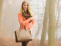 Szczęśliwa mody kobieta z torebką w jesień parku Obrazy Stock
