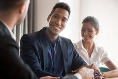 Szcz??liwa multiracial para konsultuje przy specjalisty biurem zdjęcia stock