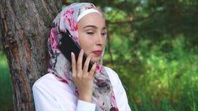 Szczęśliwa Muzułmańska kobieta opowiada na mobilny plenerowym zbiory