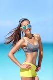 Szczęśliwa napad plaży dziewczyna jest ubranym okulary przeciwsłonecznych w sprawności fizycznej sportswear fotografia royalty free