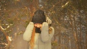 Szczęśliwa nastolatek dziewczyna cieszy się opad śniegu w zimy sosny lasowym słonecznym dniu i zakrywa z kapiszonem zbiory