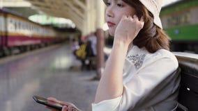 Szczęśliwa nastoletnia Azjatycka kobieta słucha muzyka z hełmofonami i czeka w dworca lecie Podróży Thailand pojęcie zdjęcie wideo