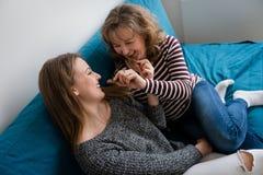 Szczęśliwa nastoletnia córka z macierzystego łasowania czekoladowym barem zdjęcia royalty free