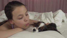 Szczęśliwa nastoletnia dziewczyna całuje i bawić się z psim Papillon w łóżko zapasu materiału filmowego wideo zdjęcie wideo