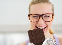 Szczęśliwa nastoletnia dziewczyna je czekoladowego baru Obrazy Stock