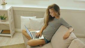 Szczęśliwa nastoletnia dziewczyna na leżance używa laptop zdjęcie wideo