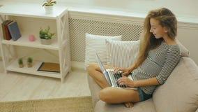 Szczęśliwa nastoletnia dziewczyna na leżance używa laptop zbiory wideo