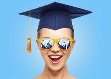 Szczęśliwa nastoletnia dziewczyna w cieniach i mortarboard kapeluszu fotografia royalty free