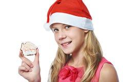 Szczęśliwa nastoletnia dziewczyna w czerwonej nakrętce z Bożenarodzeniowym ciastkiem odizolowywającym Fotografia Royalty Free