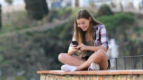 Szczęśliwa nastoletnia dziewczyna wyszukuje telefon zawartość na wypuscie zbiory