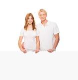 Szczęśliwa nastoletnia para pozuje z białym sztandarem Zdjęcia Stock