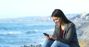 Szczęśliwa nastoletnia wyszukuje telefon zawartość na plaży zbiory