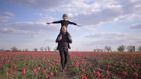 Szczęśliwa niemiec rodzina, młoda samiec z dziecko chłopiec rozszerzania się rękami popierać kogoś obsiadanie na ramionach chodzi zdjęcie wideo