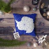 Szcz??liwa nowy rok etykietka z Antarctica flag? na poduszce Bo?enarodzeniowy dekoracji poj?cie na drewnianym stole z uroczymi pr zdjęcie royalty free