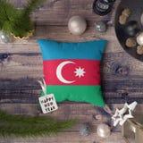 Szcz??liwa nowy rok etykietka z Azerbejd?an flag? na poduszce Bo?enarodzeniowy dekoracji poj?cie na drewnianym stole z uroczymi p obrazy royalty free