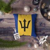 Szcz??liwa nowy rok etykietka z Barbados zaznacza na poduszce Bo?enarodzeniowy dekoracji poj?cie na drewnianym stole z uroczymi p zdjęcia stock