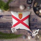 Szczęśliwa nowy rok etykietka z bydło flagą na poduszce Bo?enarodzeniowy dekoracji poj?cie na drewnianym stole z uroczymi przedmi zdjęcie stock