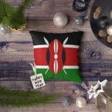 Szczęśliwa nowy rok etykietka z Kenja flagą na poduszce Bo?enarodzeniowy dekoracji poj?cie na drewnianym stole z uroczymi przedmi obraz royalty free
