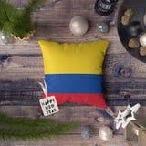 Szcz??liwa nowy rok etykietka z Kolumbia flag? na poduszce Bo?enarodzeniowy dekoracji poj?cie na drewnianym stole z uroczymi prze fotografia royalty free