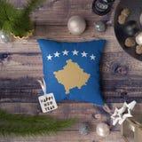 Szczęśliwa nowy rok etykietka z Kosowo flagą na poduszce Bo?enarodzeniowy dekoracji poj?cie na drewnianym stole z uroczymi przedm obraz royalty free