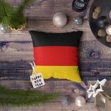 Szczęśliwa nowy rok etykietka z Niemcy flagą na poduszce Bo?enarodzeniowy dekoracji poj?cie na drewnianym stole z uroczymi przedm obraz stock