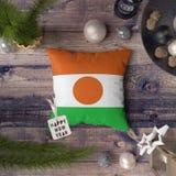 Szcz??liwa nowy rok etykietka z Niger flag? na poduszce Bo?enarodzeniowy dekoracji poj?cie na drewnianym stole z uroczymi przedmi obrazy royalty free