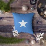 Szcz??liwa nowy rok etykietka z Somalia flag? na poduszce Bo?enarodzeniowy dekoracji poj?cie na drewnianym stole z uroczymi przed fotografia stock