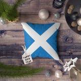 Szcz??liwa nowy rok etykietka z Szkocja flag? na poduszce Bo?enarodzeniowy dekoracji poj?cie na drewnianym stole z uroczymi przed zdjęcie royalty free
