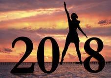 Szczęśliwa nowy rok karta 2018 Sylwetka młoda kobieta na plaży jako część liczby 2018 znak Obrazy Royalty Free